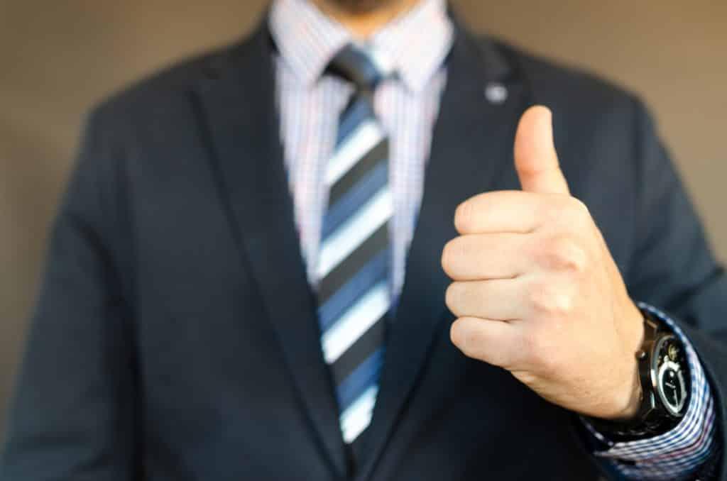 GTA Seguro Viagem - homem de terno azul fazendo sinal