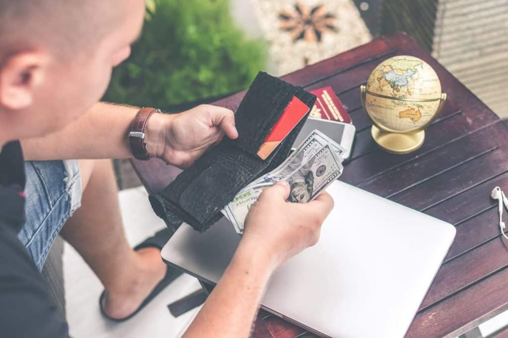 Carteira com dinheiro e mapa múndi
