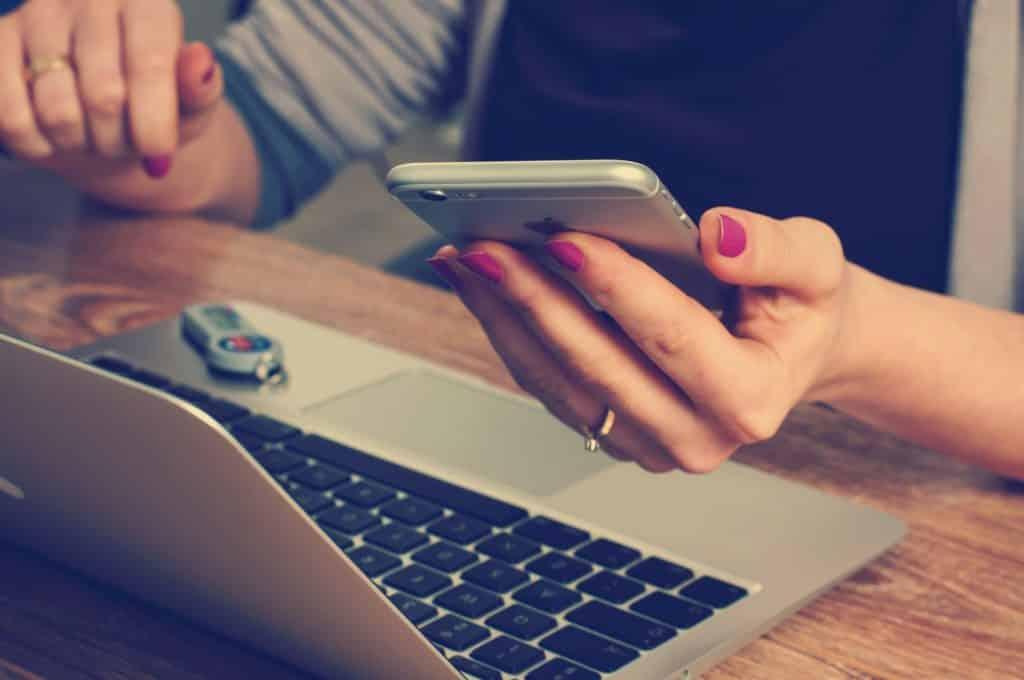 mulher com unhas feitas pintadas de vermelho segurando um celular em frente a um computador para acionar o seguro viagem berlim