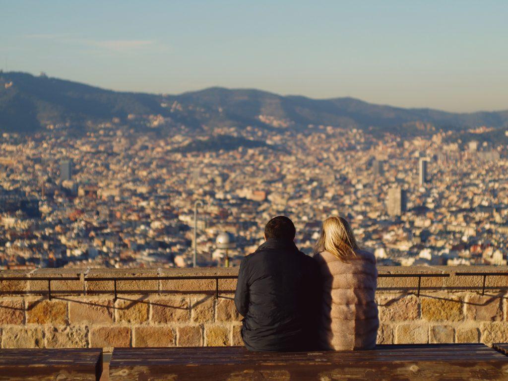 Casal sentado com roupa de frio com vista para Barcelona