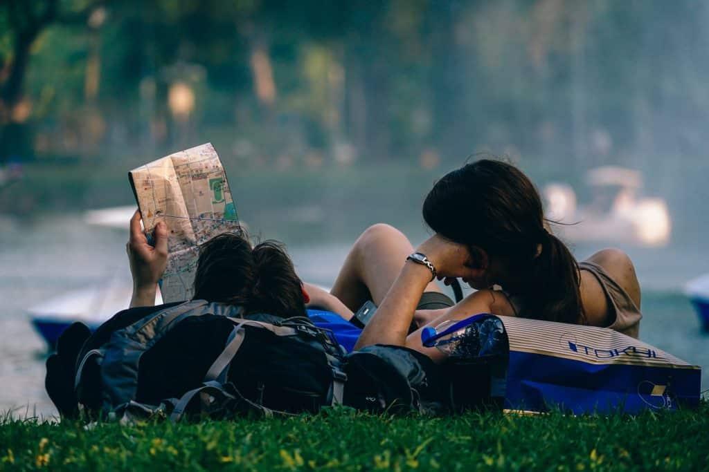 casal relaxando na grama e olhando para mapa para planejar sua viagem segurado com a Travel Ace