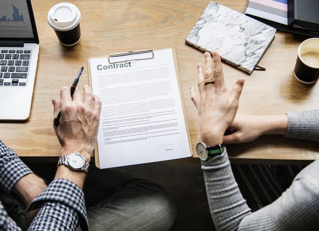 como fazer cotação de seguro viagem- ve-se na foto um casal argumentando com um contrato sobre a mesa