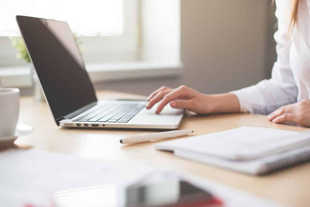 mulher sentada a mesa em frente ao computador escolhendo um seguro viagem gestante